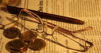 óculos dinheiro e caneta